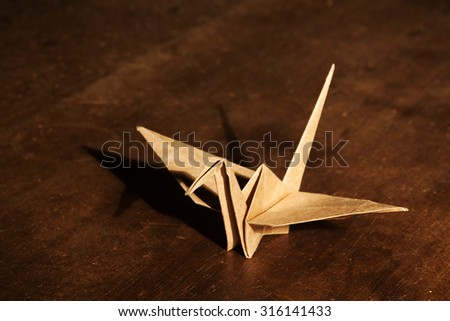 Origami crane isolated on wooden background - stock photo