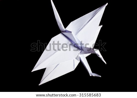 Origami crane made from white paper on black background with reflection. - stock photo