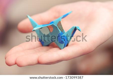 Origami crane on child hand - stock photo