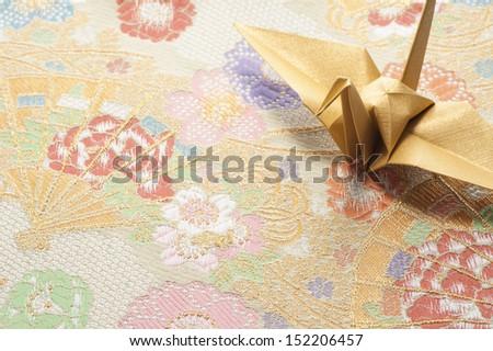 origami crane on japanese textile background - stock photo