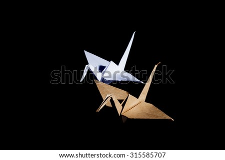 Origami cranes made from brown recycle paper isolated on black background - stock photo