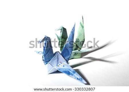 Origami cranes made of brazilian money. - stock photo