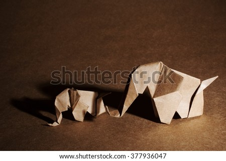 Origami elephants made of brown paper over craft background. - stock photo
