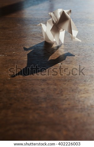 Origami elephants made of white paper over wooden background. - stock photo