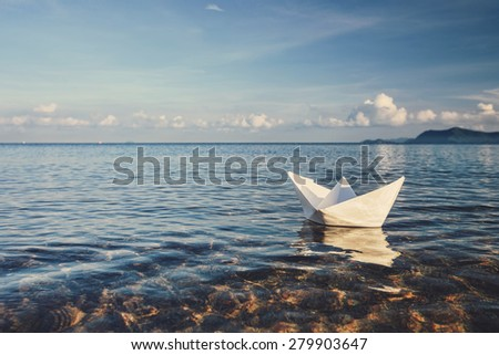 origami paper sailboat sailing on blue water - stock photo