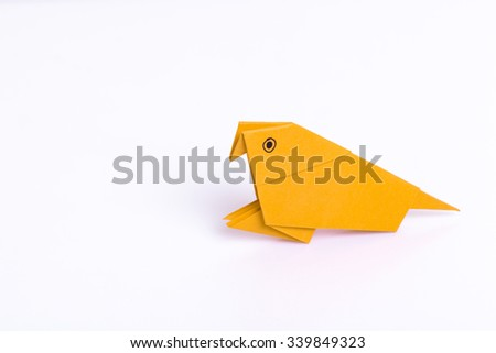 Origami parrot from paper color on white background. - stock photo