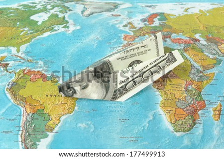 Origami plane made from dollars on the map - stock photo