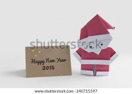 Origami Santa Claus paper craft with a Happy New Year 2015 card - stock photo
