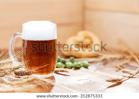 Original bavarian Oktoberfest background.  Glass of beer on wooden background with hops, wheat and Pretzel. Mug of beer festival template background. - stock photo
