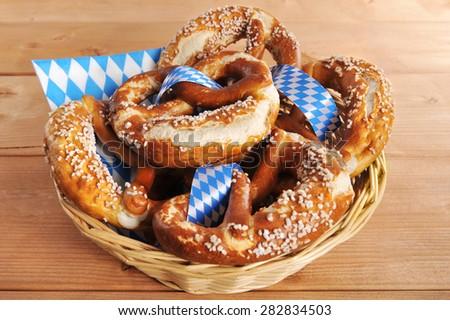 original bavarian Oktoberfest salted soft pretzels in a basket on wooden board - stock photo