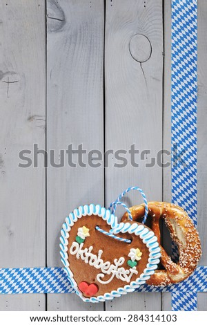 original bavarian salted soft pretzels Oktoberfest gingerbread heart from Germany in front of wooden board - stock photo