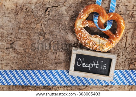 original bavarian salted soft pretzels with blackboard from Germany on real brown tree bark - stock photo