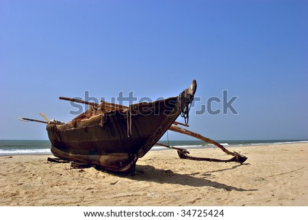 Original fishing boat on vast empty sand beach in Goa, India - stock photo