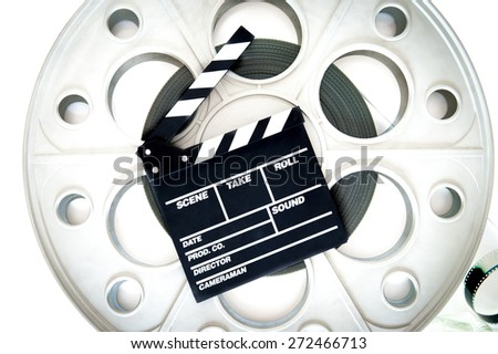 Original old big movie reel for 35 mm cinema projector loaded with film, with clapper board on neutral background - stock photo