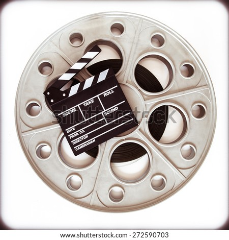 Original old big movie reel for 35 mm cinema projector loaded with film, with clapper board on neutral background vintage color effect - stock photo
