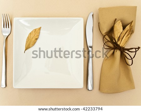 original table serving with golden bay leaves in serviette and cord near plate, knife and fork at beige - stock photo