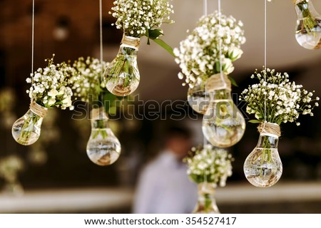 Original wedding floral decoration in the form of mini-vases and bouquets of flowers hanging from the ceiling - stock photo