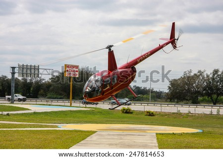 ORLANDO, FL, USA - MARCH 10, 2008: Red tourist helicopter takes off  for sightseeing journey in Orlando, USA on March 10, 2008.  - stock photo