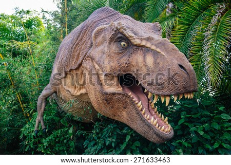 ORLANDO, FLORIDA NOVEMBER 6th: A T-Rex stands between the bushes with his mouth open showing his teeth in theme park Universal Orlando, Islands of Adventure - stock photo