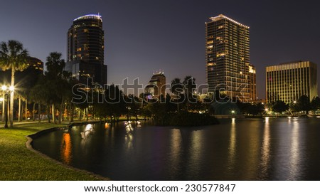 Orlando Lake Eola in the evening with urban skyscrapers and clear dark sky with moon. - stock photo