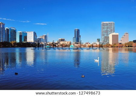 Orlando Lake Eola in the morning with urban skyscrapers and clear blue sky with swan. - stock photo