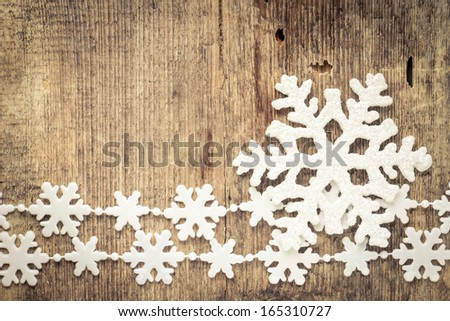 Ornament with snowflakes over rustic wooden background - stock photo