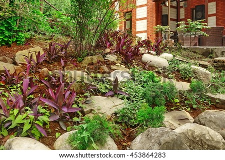 Ornamental Backyard Garden With Small Hill, Tropical Plants, Flowers And Natural Stone Landscaping.  House Veranda With Rattan Furniture In The Background - stock photo