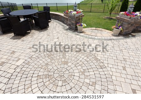 Ornamental brick paved outdoor patio with a circular design in the bricks with dining furniture and colorful flowers in flowerpots flanking steps and an entrance, view from above after rain - stock photo