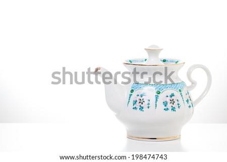 Ornamental Teapot  on white background. Porcelain dishes. Kitchenware. Decorative background.Tableware. Tea time. - stock photo