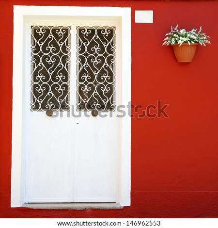 ornamental white double door and vivid red wall with hanging  flowerpot, Burano village on venetian lagoon, Venice , Italy, Europe - stock photo