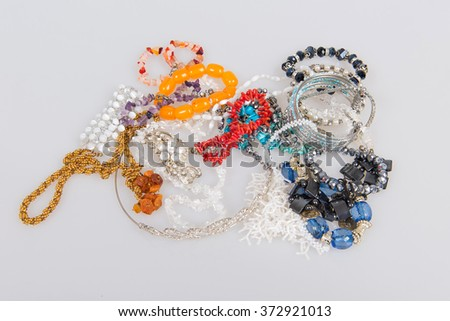 Ornaments on a white background, jewelery exhibition, than to adorn themselves at the festival, a collection of necklaces and bracelets made of natural stones, pearl bracelet, amber beads, - stock photo