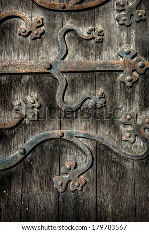 Ornate and weathered church door hinge pattern. - stock photo