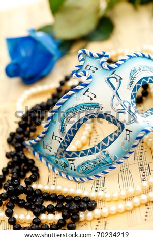 Ornate carnival mask on a music paper with rose, white and black pearls - stock photo