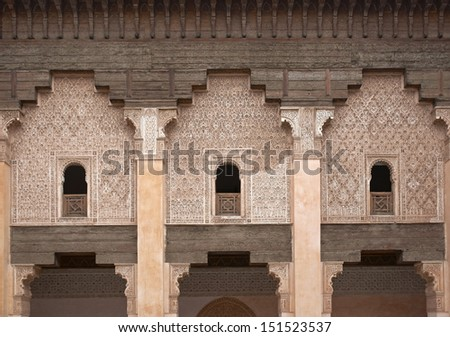 Ornate carving on the plastered walls and on the woodwork in the courtyard of the historic Ben Youssef Madrasa in the ancient heart of Marrakech in Morocco - stock photo