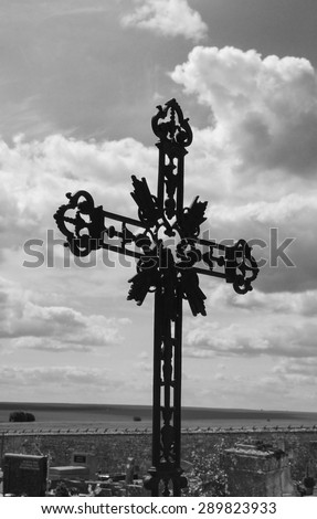 Ornate cast iron cross at French cemetery and sun glow through the clouds. Aged photo. Black and white. - stock photo