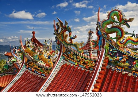 Ornate Chinese Temple detail in the sky. - stock photo