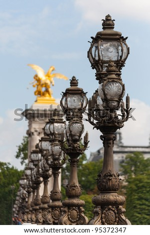 Ornate lampposts on Alexander III bridge in Paris shot with a shallow depth of field - stock photo
