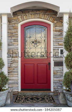 Ornate red front door of a home. A red door to a family home, framed by stone detail and two white columns. The door has an ornate pattern. Also seen is doormat, and two potted trees.  - stock photo