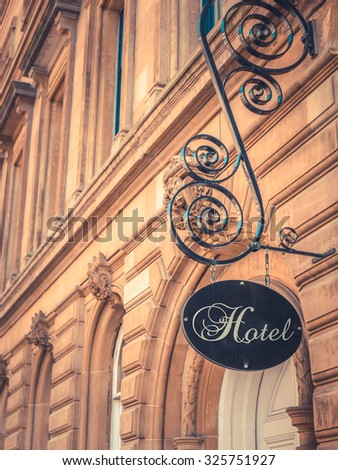 Ornate Sign For Luxury Hotel Outside Beautiful Sandstone Building - stock photo