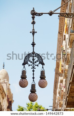 Ornate street lamps hanging from walls of buildings in Barcelona - stock photo