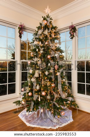 Ornately decorated and lit Christmas tree in the corner of a modern family home with trees lit by setting sun - stock photo