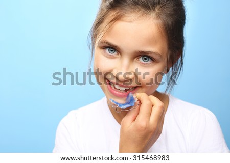 Orthodontics.Pretty girl with colored orthodontic appliance  - stock photo