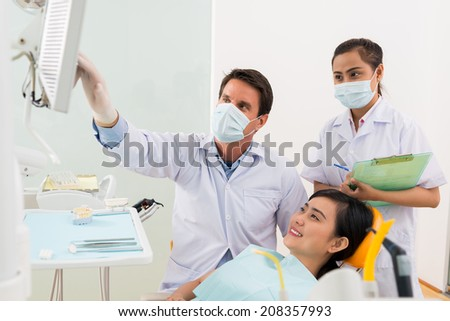 Orthodontist showing something on the monitor to female patient - stock photo
