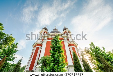 Orthodox church facade surrounded by vivid green trees and beautiful blue sky on a warm spring day - stock photo