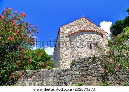 Orthodox church with stone walls amongst Mediterranean vegetation, Montenegro - stock photo