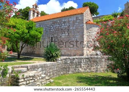 Orthodox monastery church surrounded by Mediterranean vegetation, Montenegro - stock photo