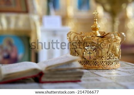 Orthodox wedding ceremonial crown and the Bible, ready for a crowning ceremony. - stock photo