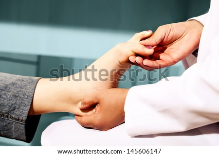 Orthopedic doctor in his office checking feet - stock photo