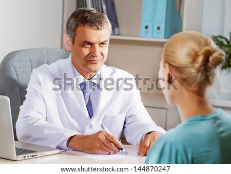 Orthopedic doctor in his office with the patient - stock photo