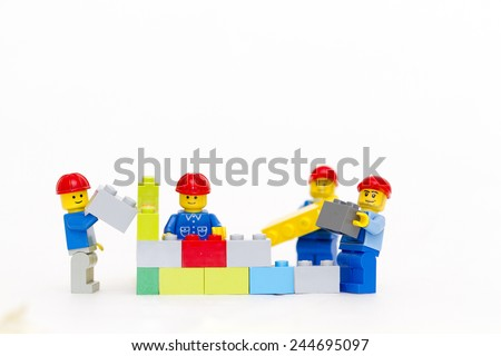 Orvieto, Italy - January 16th 2015: group of workman Lego mini figure build a wall. Lego is a popular line of construction toys manufactured by the Lego Group - stock photo
